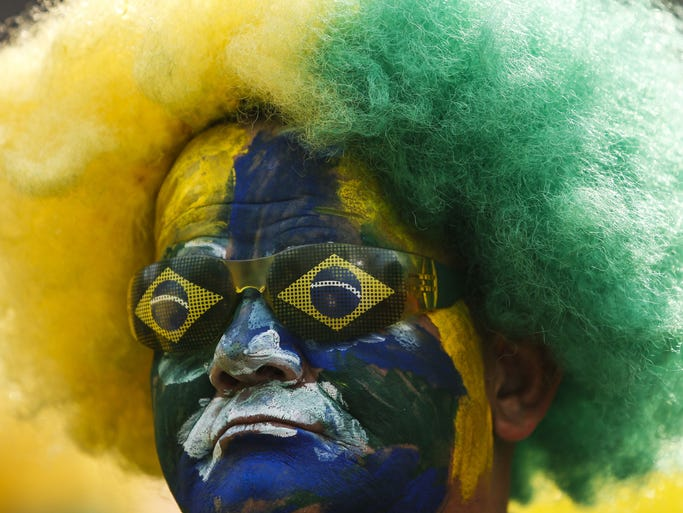 Brazil's supporters pose as they wait to watch the 2014 FIFA World Cup Brazil vs Mexico match at the FIFA Fan Fest public viewing event in Sao Paulo, Brazil on June 17, 2014. AFP PHOTO/Miguel SCHINCARIOL        (Photo credit should read Miguel Schincariol/AFP/Getty Images)