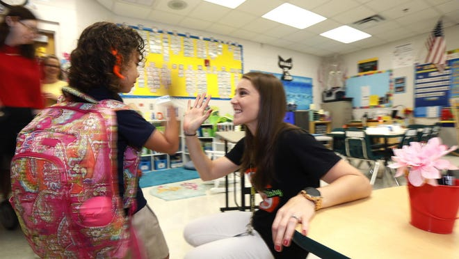 Lillie Martinez, 6, gets greeted by her first grade teacher Lauren Schicker while heading back to school at Citrus Grove Elementary in DeLand, Monday, August 13, 2018.