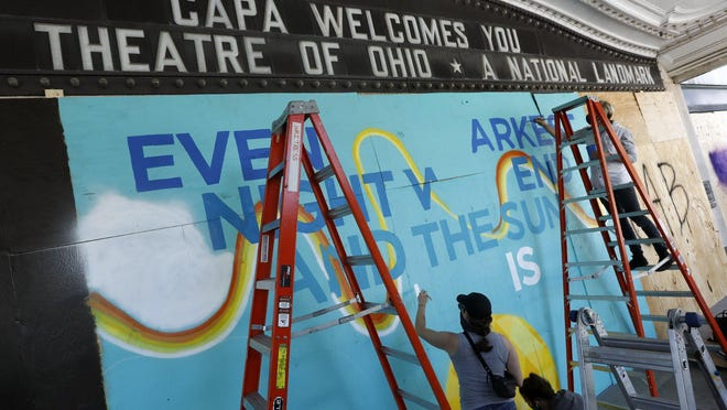 "Artists work together to paint the words, ""Even the darkest night will end and the sun will rise,"" from ""Les Miserables,"" on the boarded-up Ohio Theatre earlier this week."