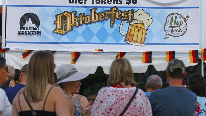 Festival goers line up to refill their cups during Oktoberfest, Saturday, Sept. 21, 2019, in Cuyahoga Falls, Ohio. The 2020 event has been canceled because of the coronavirus outbreak, organizers announced Wednesday.