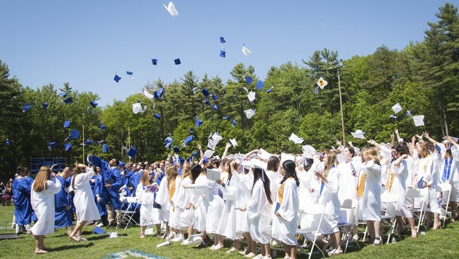 Graduates toss their caps in the air at the conclusion of Kennebunk High School's graduation ceremony in 2019.