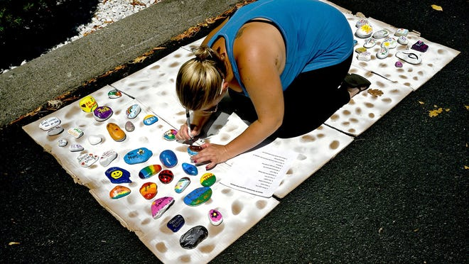 """Lisa Trusas, a recovery coach for Community Impact Inc.'s Regional Substance Navigation Program, adds the #rsnp hashtag to the back of a rock during a """"Recovery Rocks"""" rock painting event Saturday morning at the Community Impact office on Main Street in Milford. About 40 people decorated the rocks with inspirational messages. They will be distributed throughout Milford in coming days. Community Impact provides services for people struggling with addiction and their families."""