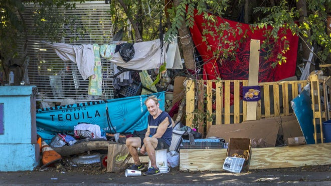 Christopher Doolin sits on the sidewalk along Barton Springs Road on Oct. 21.  Local nonprofit Save Austin Now wants to reinstate Austin's homeless camping ban.
