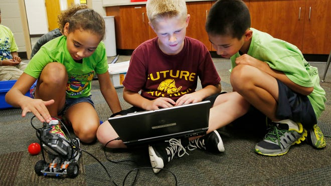Eden Jones, left, Ethan Beldsoe and Robert Kock use a laptop computer to program movement in their Lego robot Friday in Beau Scott's high-ability classroom at Dayton Elementary School. Scott uses a blog to keep parents and students updated on what is happening. Jones and Kock are fourth-graders. Bledsoe is a fifth-grader.