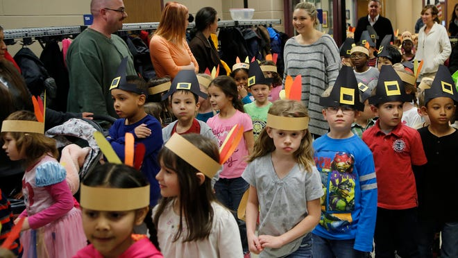 Kindergarten students wear paper hats of Pilgrims and Native Americans as they enter the cafeteria.