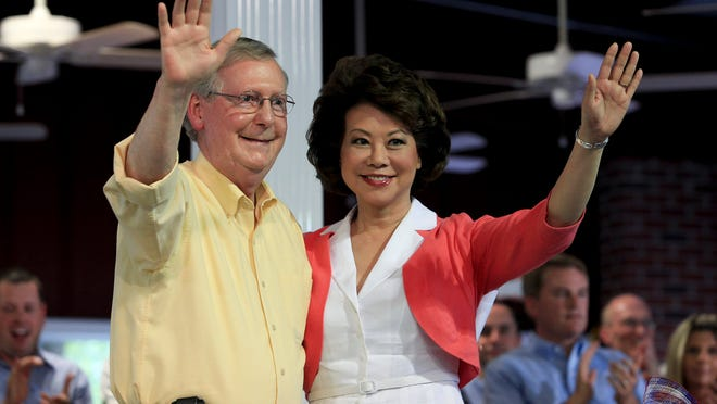 U.S. Sen. Mitch McConnell, left, and his wife Elaine Chao waved to the crowd following his speech at the Fancy Farm Picnic.  Aug. 2, 2014
