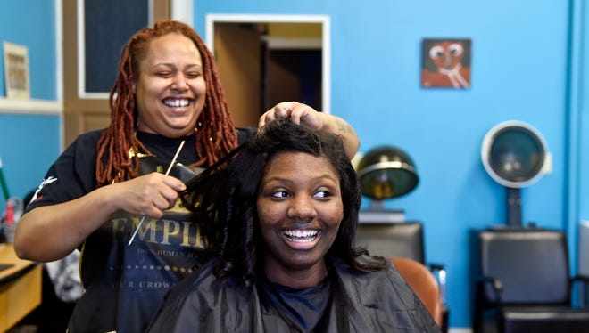 """Shaniece Holmes-Brown gets her hair done by Marisa Wilson, owner of Beneath the Surface Salon, before William Penn's prom Saturday, May 13, 2017. York City School District Police officer Britney Brooks decided to give Holmes-Brown, 18, a """"dream prom"""" when she learned Holmes-Brown's original prom plans had fallen through. Holmes-Brown, who will be the first in her family to attend college, was given a dress and provided with hairstyling, a makeover, a date, a police escort and a serenade performed by Brooks upon her arrival at William Penn's prom at Wisehaven Event Center in Windsor Township."""