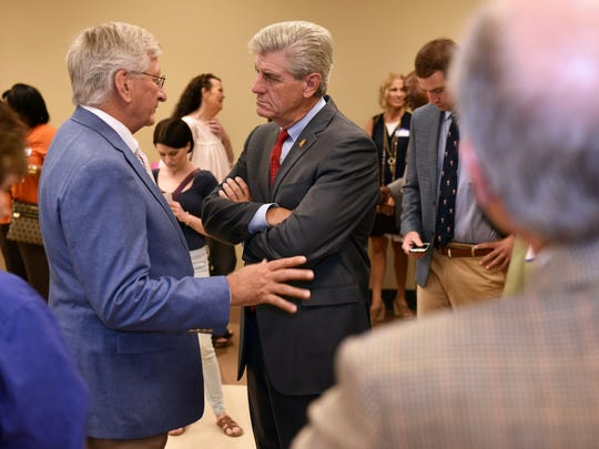 Child Protection Services Director Dr. David Chandler, left, and Gov. Phil Bryant speak at a Rescue 100 Vision meeting Friday at the Gartin Justice Building Jackson.