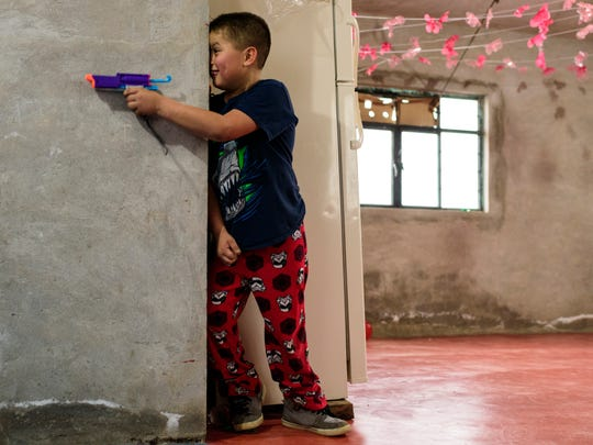 Anthony Cuahua, 8, hides from his cousin, Emanuel Matlatecatl, 6, as they play with toy guns inside his sparsely furnished home in rural Atlanca, a town located about an hour away from Orizaba, Mexico, on Jan. 12 Although the four Cuahua children do not yet understand Spanish, they spent time bridging the language barrier with their cousins by spending hours laughing and playing together.