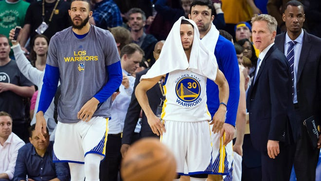 Golden State Warriors center JaVale McGee (1), guard Stephen Curry (30), center Zaza Pachulia (27) and head coach Steve Kerr on the sideline at the end of the game against the Boston Celtics at Oracle Arena.