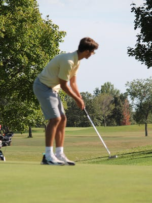 Mercer County player, Robbie Holzschlag, watches his putt during the meet on Wednesday.