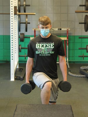 Brady Kelley, incoming senior, exercises his legs while holding onto weights during a conditioning session on Monday morning at Wethersfield High School.