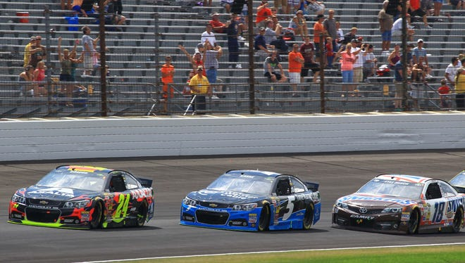 Jeff Gordon makes the pass in turn one on Kasey Kahne for the win at  the Brickyard 400  NASCAR  race July 27, 2014 at The Indianapolis Motor Speedway.