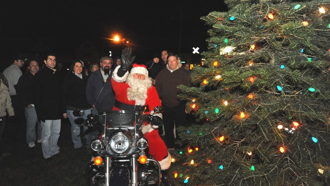 Santa waves to visitors during a Christmas tree lighting event at the Buena Borough municipal building in Minotola on Saturday, December 10, 2011.