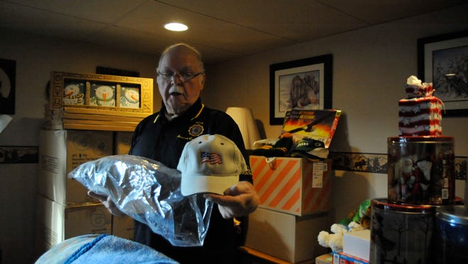 Ron Miller, American Legion Wood County commander, shows off an embroidered cap , one of hundreds of presents he gave last year at the Veterans Home at King. This year, there were too many gifts to store them in his basement, he said.
