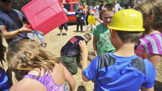 Children dunk Fire Information Officer Mike Theune.