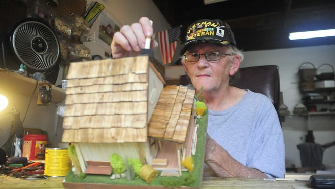 Dave Woodruff stains one of his miniature barns Tuesday in Galion.