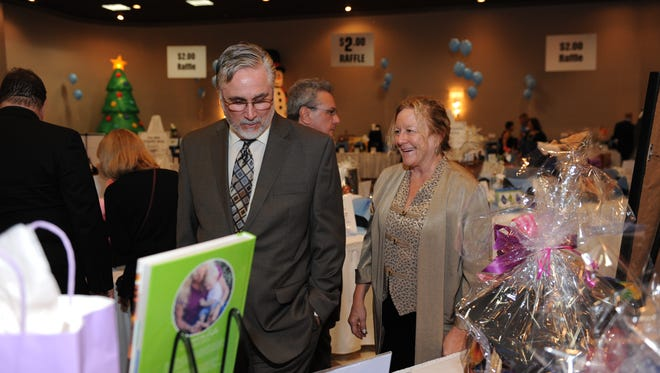 Tom and Sandy Leighton browse the vast amount of auction items at this years Plymouth Chamber event.
