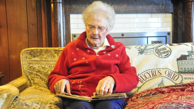 Eleanor Miller looks over a scrapbook she kept while serving as a Marine during WWII.
