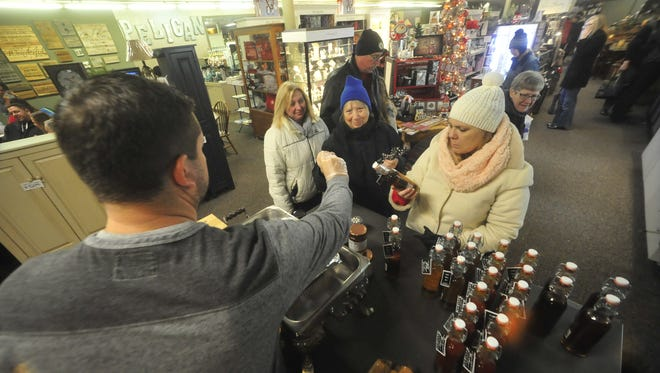 Josh Leitzy, owner of Amish Vault in Bucyrus, hands out samples to guests Thursday during the Candlelight Christmas event downtown.