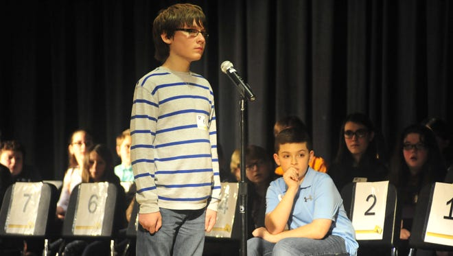Luke Biederman waits for the judges' response after winning the Crawford County Spelling Bee as second place finisher Drew Johnson looks on.