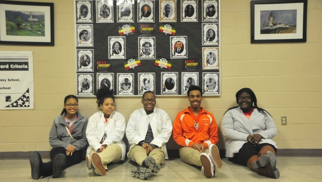 Officers of the Black Culture Club sit by a display of influential African Americans inside Mansfield Senior High.