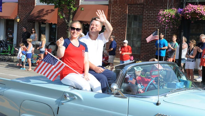 South Lyon Mayor Dan Pelchat and fiancee Meredith Pedersen wave to the crowd at the Memorial Day parade.