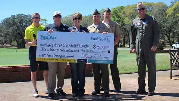 Left to right: Stu Ramsey, president and CEO of Pen Air, presents a donation to Mark Harden and Amanda Shadden, of the Navy-Marine Corps Relief Society of Pensacola. Also attending were Lt. Col. Frost, Gunnery Sgt. Marks and Capt. Christopher Martin, commanding officer of Pensacola Naval Air Station.