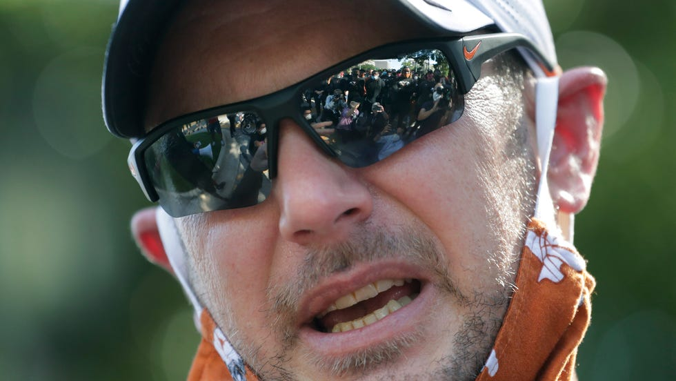 FILE - Texas football players are reflected in the glasses of coach Tom Herman in Austin, Texas last year after they marched to the State Capitol during a protest over the death of George Floyd.