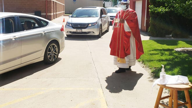 Cars lined up around the block on Sunday as drivers waited to take communion at the St. John Paul II Parish in Kewanee. Father Johdemesani Zilimu wore a face shield to give communion to waiting drivers and kept hand sanitizer nearby.