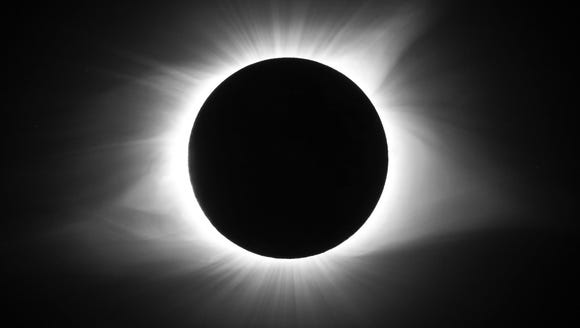 The corona of the sun is visible around the moon during