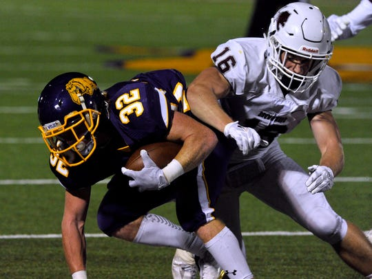 Wylie High School tailback Cason Grand is bumped by