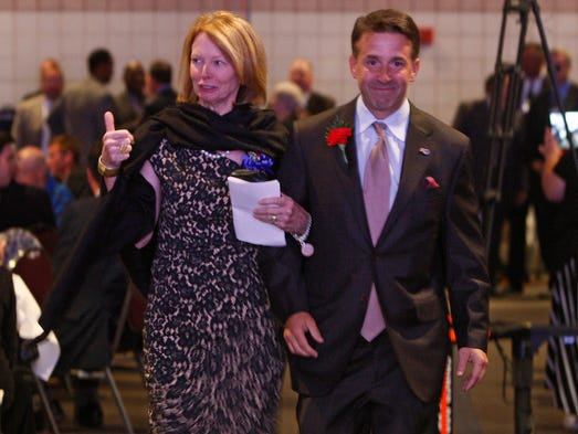 Mary Wilson, widow of Buffalo Bills owner Ralph Wilson, gives a warm thumbs-up to the surprised guests in attendance as she walks the guests isle with Russ Brandon, President of the Bills, at the Rochester Press-Radio Club 65th Annual Day of Champions dinner Monday, June 9, 2014 in downtown Rochester.  Mrs. Wilson was accepting the Major Donald Holleder Award that was given to her husband.