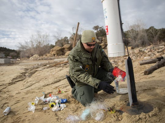 Navajo Lake State Park Superintendent Christopher Smith removes trash and fishing lines from a recycling bin on Jan. 12 at the park.