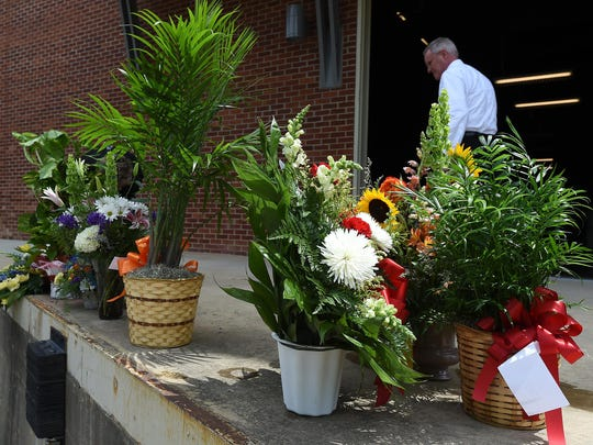 John Barnes of Roller Funeral Home takes flowers from The Sheid after the memorial service for Jim Gaston.