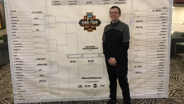 William Saxman stands in front of a giant NCAA Tournament bracket in the South Carolina team hotel in Greenville, South Carolina, this weekend.