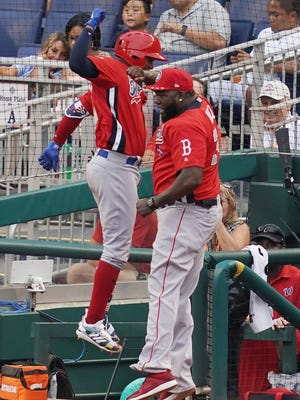 World Team Yusniel Diaz, of the Los Angles Dodgers, left, celebrates his home run with World Team manager David Ortiz in the seventh inning of the All-Star Futures baseball game against the U.S. Team, Sunday, July 15, 2018, at Nationals Park, in Washington. The the 89th MLB baseball All-Star Game will be played Tuesday. (AP Photo/Carolyn Kaster)