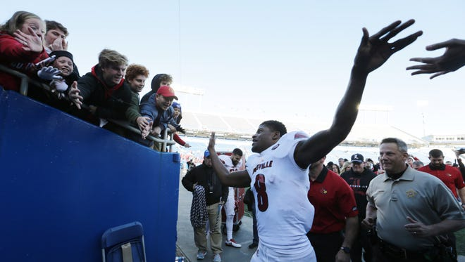 Louisville's Lamar Jackson celebrated with fans who waited for him after he lead his team to a 44-17 victory over UK, in Lexington. Nov. 24, 2017.