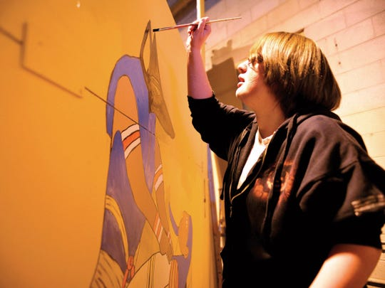 Emily Hamblin of Farmington paints a room at a haunted house at an old warehouse on Airport Drive and West Arrington Street in this Daily Times file photo.