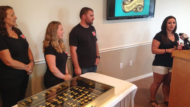 Members of the Schmitt family display their find of Spanish gold coins and chains from the sunken 1715 Fleet.