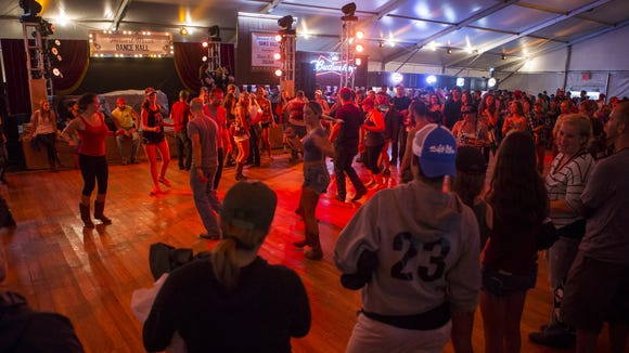 Spectators gather around line dancers in the Harvest Moon Dance Hall at the Big Barrel Country Music Festival on Saturday.