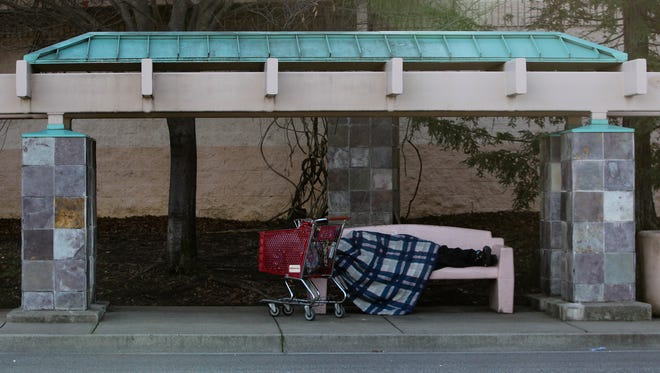 A person sleeps at a bus stop Friday off Placer Street prior to the arrival of an intense winter storm.