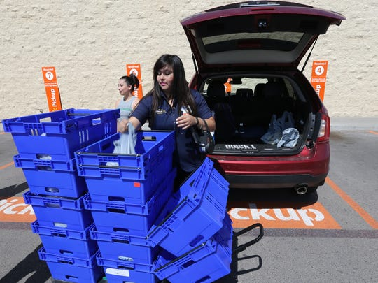 Lessley Almaguer, right, loads Janet Villa's car Wednesday in the pickup area of the Wal-Mart at 12236 Montana Ave.