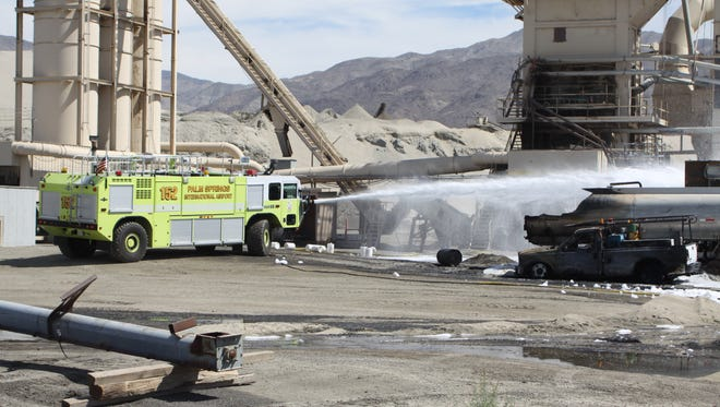Firefighters use foam to prevent vapors from entering the air near the Skanska asphalt plant north of Indio Monday. A gas tanker caught fire and created black smoke that was visible across the Coachella Valley.