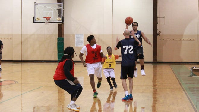 Youth in Keep My Hood Good play basketball against members of the Jackson Police Department at the T.R. White Sportsplex on Saturday.