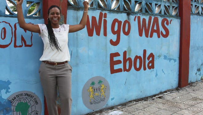 "Brandy Maddox stands on a street at Freetown, Sierra Leone. The writing on the wall translates to ""We will defeat Ebola."" Signs such as those in Krio and English were a reminder that everyone played a role in the fight against the Ebola virus."