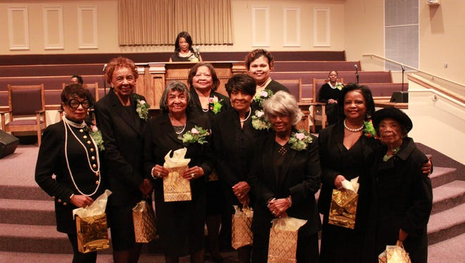 Golden members who have been a part of Alpha Kappa Alpha Sorority for more than 50 years stand with Tracy Perkins, chapter president.