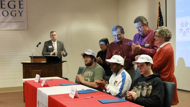 Grant Coleman, Fortina Moba and Gus Montgomery finish signing their letters of intent to attend the Tennessee College of Applied Technology on Thursday in Jackson.