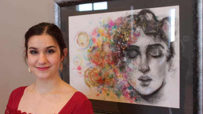 Elizabeth Rast, 17, poses with 'Chimera,' a mixed media piece that won 'best of show' at the West Tennessee Regional Student Art Exhibition.