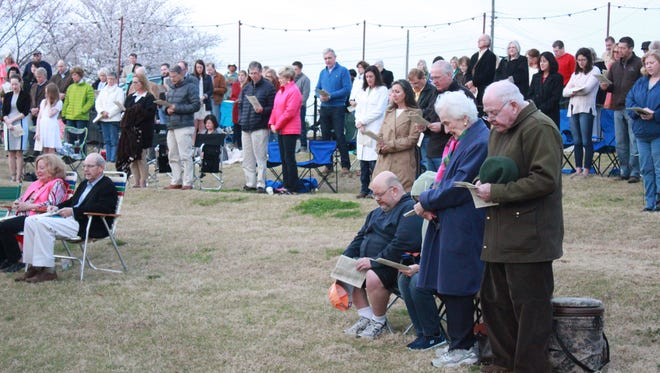 People pray the Lord's Prayer Sunday at an Easter Sunrise Service at the downtown AMP.